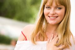 photo of attractive blond lady looking at camera with smile - stock photo