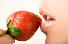 image of tasty strawberry near female mouth - stock photo