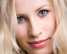 Close-up of young beautiful blue-eyed woman looking at camera with smile Stock Photos