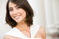 Stock Photo of portrait of smiling lady with brown hair on the background of columns