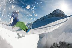 photo of snowboarder over snowdrift going in for sport in winter - stock photo