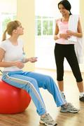 Image of two girls talking and looking at each other in the gym Stock Photos