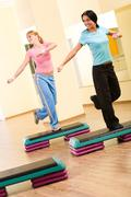 Two sporty women practicing physical exercises standing on one leg and looking t Stock Photos