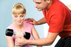 image of pretty girl exercising with barbell in hand while the trainer assisting - stock photo