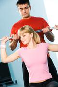 portrait of sporty girl holding dumbbell assisted by her trainer - stock photo