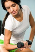 close-up of young woman sitting with barbell in hand and lifting it - stock photo