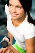Young brunette doing physical exercises with barbell in hand Stock Photos