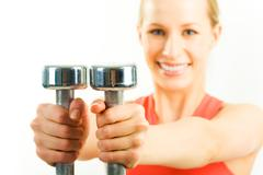 Stock Photo of horizontal image of metal dumbbells in woman's hands