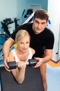 Blonde woman lifting weight with man assisting her in the sport club Stock Photos