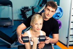 Image of trainer assisting young woman in the health club Stock Photos