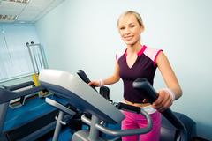 Image of pretty girl in sportwear on the treadmill running Stock Photos