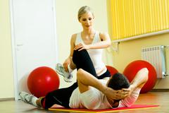 photo of sportsman doing physical exercise while his pretty instructor helping h - stock photo