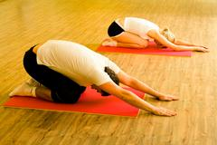 Image of man and woman doing physical exercises on mats in the sports club toget Stock Photos