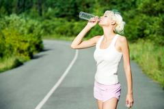 Photo of attractive young girl drinking water on the road during summer hot day Stock Photos