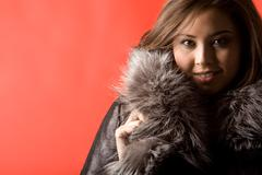 portrait of beautiful asian girl wearing fashionable fur coat and looking at cam - stock photo