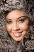 close-up of young beautiful girl wearing fur-cap and smiling - stock photo