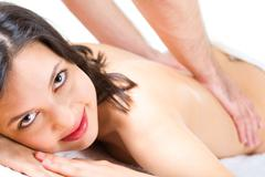 young woman looks at camera while masseuse makes massage to her - stock photo