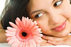 Close-up of young brunette looking at a pink daisy Stock Photos