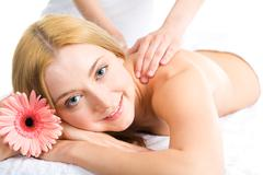 Photo of smiling woman lying in the spa salon with a flower near by Stock Photos