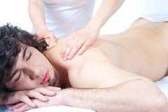 Portrait of young man with closed eyes and getting a relax massage Stock Photos
