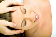 closeup of smiling female's face with closed eyes having cosmetic massage - stock photo