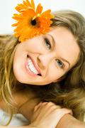 portrait of smiling young girl with orange flower in her hair looking at camera - stock photo