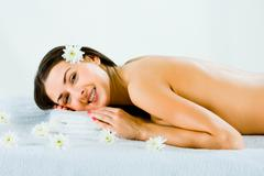 Pretty young woman lying on the towel Stock Photos
