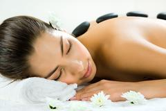 Portrait of beautiful woman sleeping during a stone massage Stock Photos