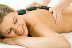 Portrait of attractive woman getting a massage at the day spa Stock Photos