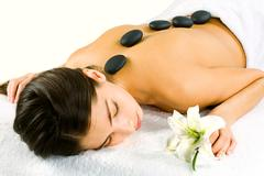Portrait of young woman at the day spa with black stones on her bare back Stock Photos