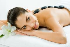 Photo of a beautiful smiling woman lying with spa stones on her back and looking Stock Photos