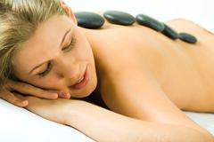 Closeup of woman's face with closed eyes and her back with spa stones on it Stock Photos