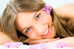 Portrait of a young fresh smiling girl lying on towel with flowers near by and i Stock Photos