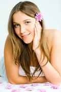 Portrait of a beautiful young woman in towel lying on the massage table before e Stock Photos