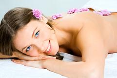 Stock Photo of horizontal photo of a pretty girl lying with flowers on her back and enjoying ar