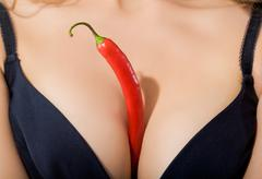 Close-up of red hot chili pepper between woman's breasts in black bra Stock Photos