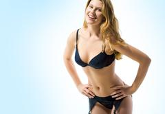 portrait of beautiful woman wearing black sexy lingerie looking with smile on bl - stock photo