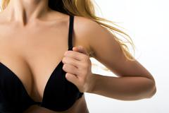 image of female's decollete with her hand on black bra - stock photo