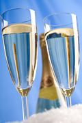 Close-up of crystal flutes with champagne on background of uncorked bottle Stock Photos