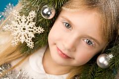 face of cute girl decorated with toys, snowflakes and artificial snow - stock photo