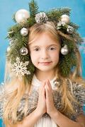 Portrait of pretty girl wearing decorations on head and keeping her palms togeth Stock Photos