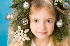 Little girl with her head decorated with new year toys looking at camera Stock Photos
