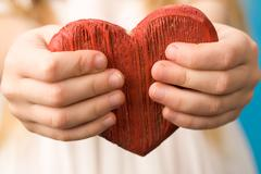 close-up of red wooden heart in child's hands showing it - stock photo