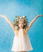 Stock Photo of portrait of joyful girl wearing white dress and wreath enjoying flurry snowfall