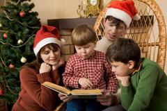 little boy surrounded by his family members trying to read book - stock photo