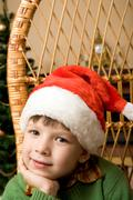 Adorable boy in santa hat touching his face and looking at camera Stock Photos