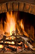 Close-up of fire in brown brick chimney set on in the evening Stock Photos
