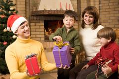 Portrait of joyful children looking at their presents surrounded by parents Stock Photos