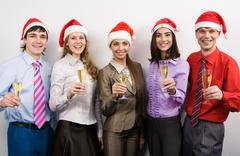 Portrait of joyful co-workers in santa caps and champagne in hands looking at ca Stock Photos