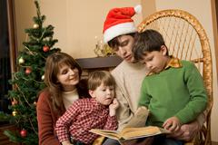 Portrait of friendly family looking into interesting book on christmas day Stock Photos